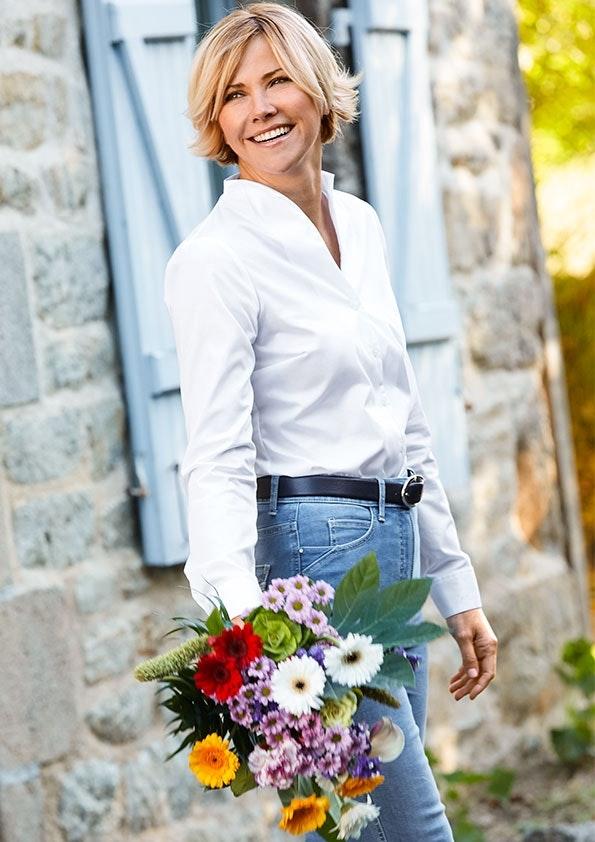 Frau in weißer Bluse und Jeans steht vor einer Häuserwand aus Stein. Sie hält einen Blumenstrauß.