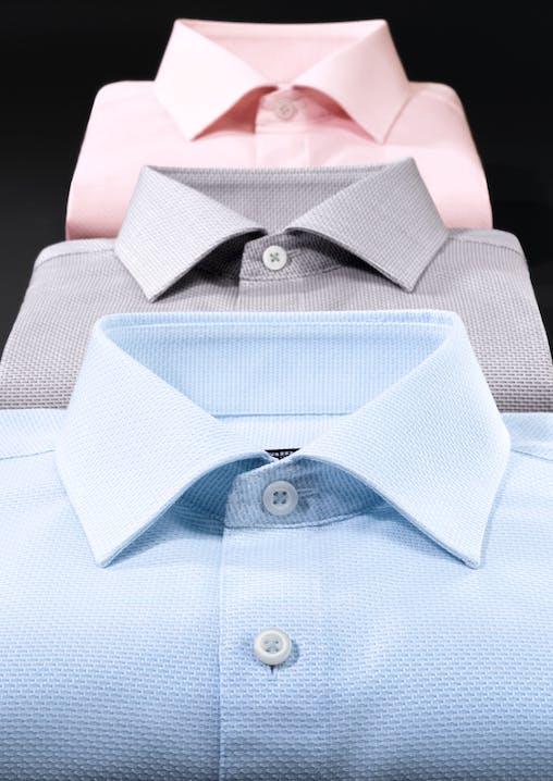 3 Hemden in den Farben hellblau, braun und rosa liegen hintereinander. Die Kragen stehen im Fokus.
