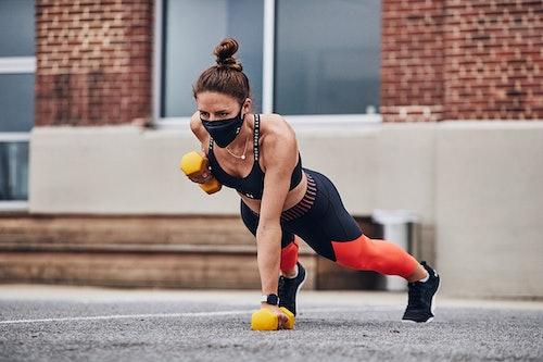 Sportlerin trainiert mit Maske