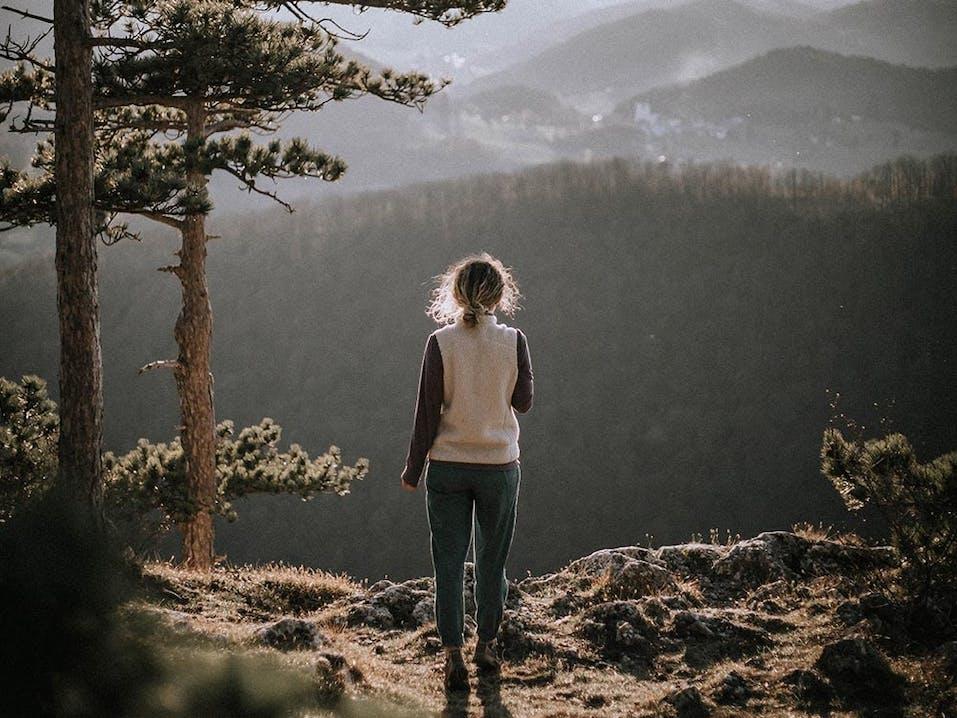 Junge Frau schaut in die Berge