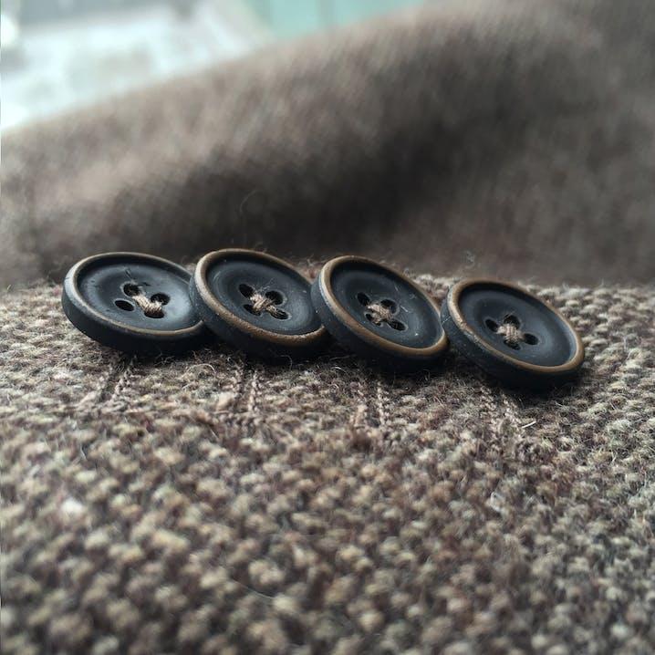Vier Knöpfe – Kissing Buttons – auf dunkelbraunem Tweed-Stoff.