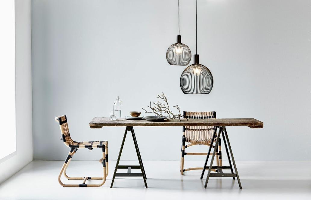 Tisch mit 2 Stühlen aus Bambus, von der Decke hängen 2 Bambuslampen, der Tisch ist sporadisch gedeckt