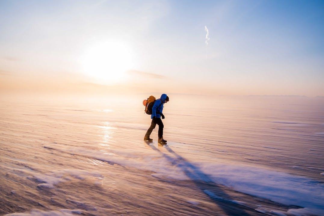 L'atleta Mammut Pro Ani Arnold cammina sulla superficie ghiacciata del Lago Baikal