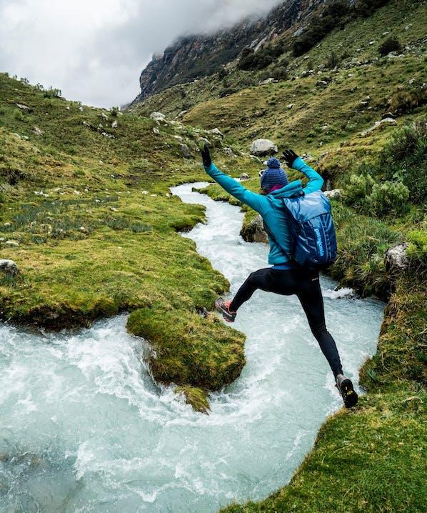 Persona che guada un fiume in ambiente montano
