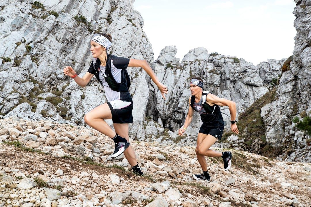 Due atleti che corrono in ambiente roccioso