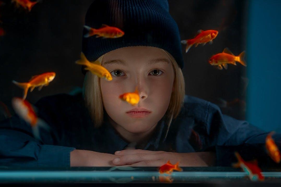 Una bambina guarda attraverso un vaso di pesci rossi