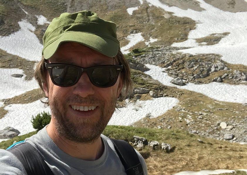 Mann mit grüner Capi und schwarzer Sonnenbrille steht vor einer Landschaft mit Steinen und etwas Schnee und lächelt