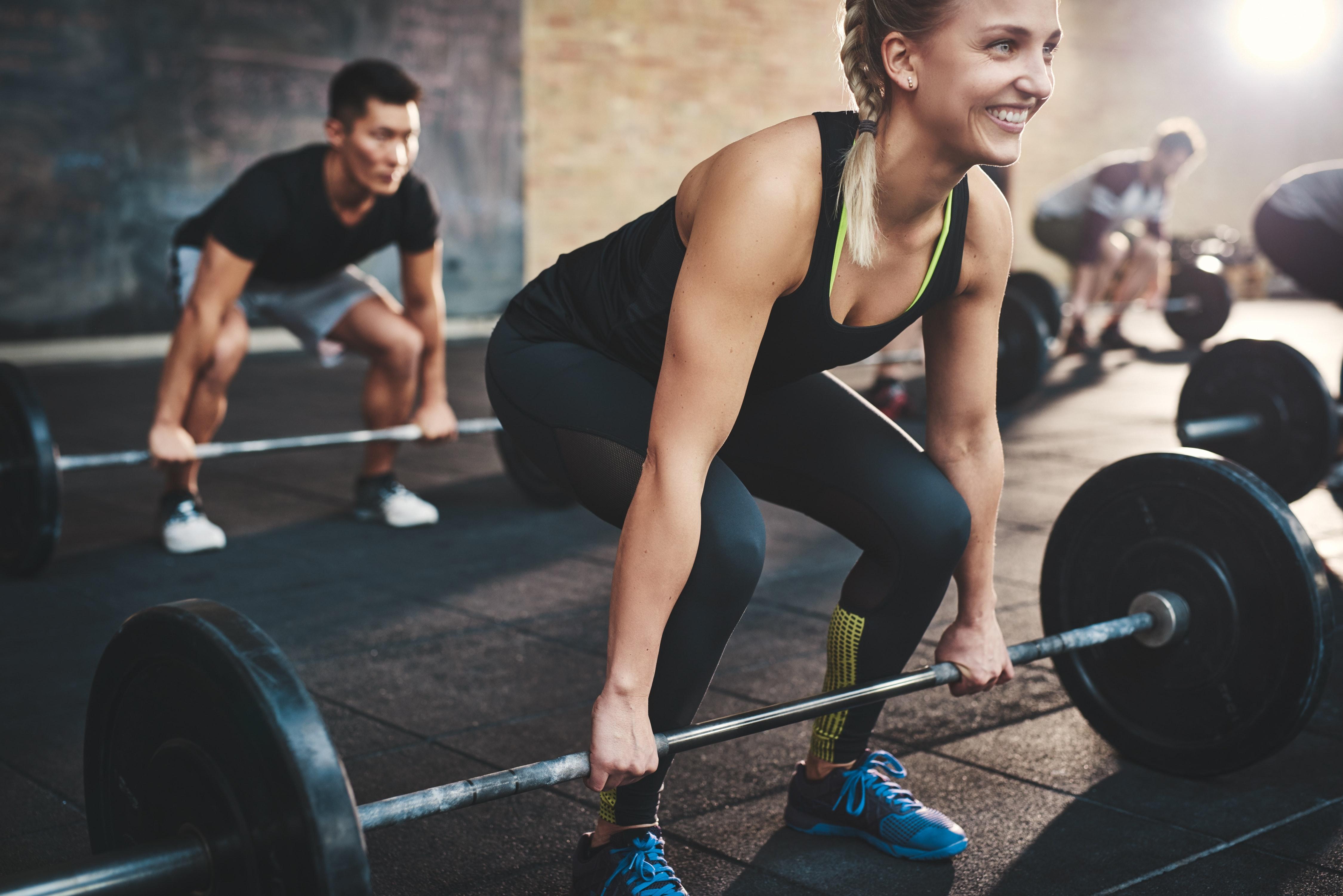 Frau mit Langhantel beim High Intensity Training