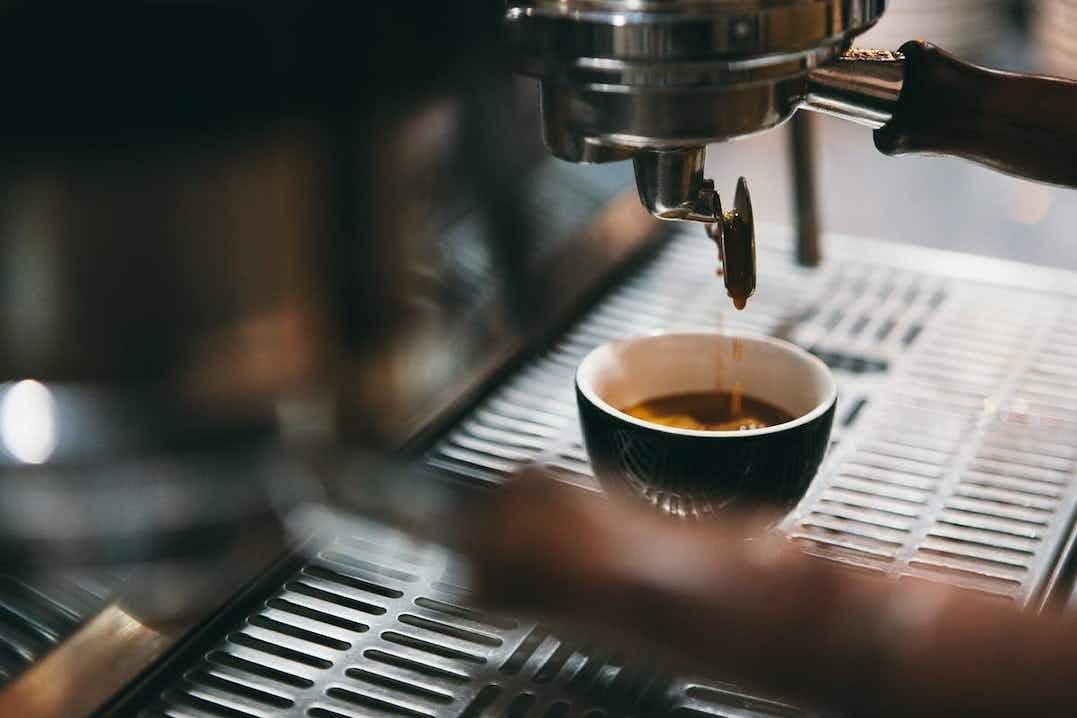 Tuore espressokahvi tippuu espressokuppiin italialaisesta kahvikoneesta