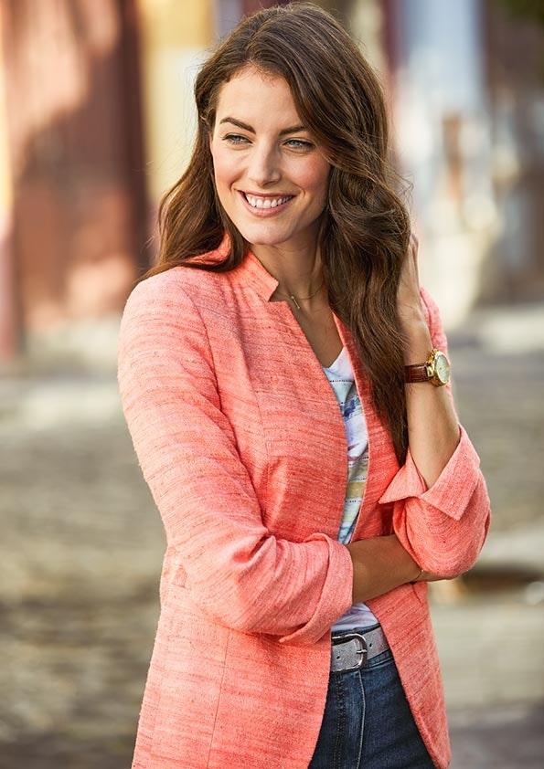 Frau mit braunen Haaren lächelt und trägt einen orangenen Blazer, T-Shirt und eine Jeans.