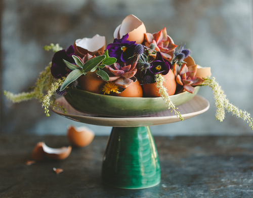 Cake stand with a green base and wooden plate, a green bowl on top with eggshells and pansies with leafy sprigs