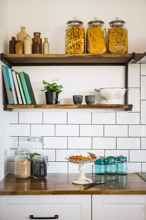 Kitchen with white tiles, surface and shelves in walnut wood, glass jars containing dried pasta and other dried foods