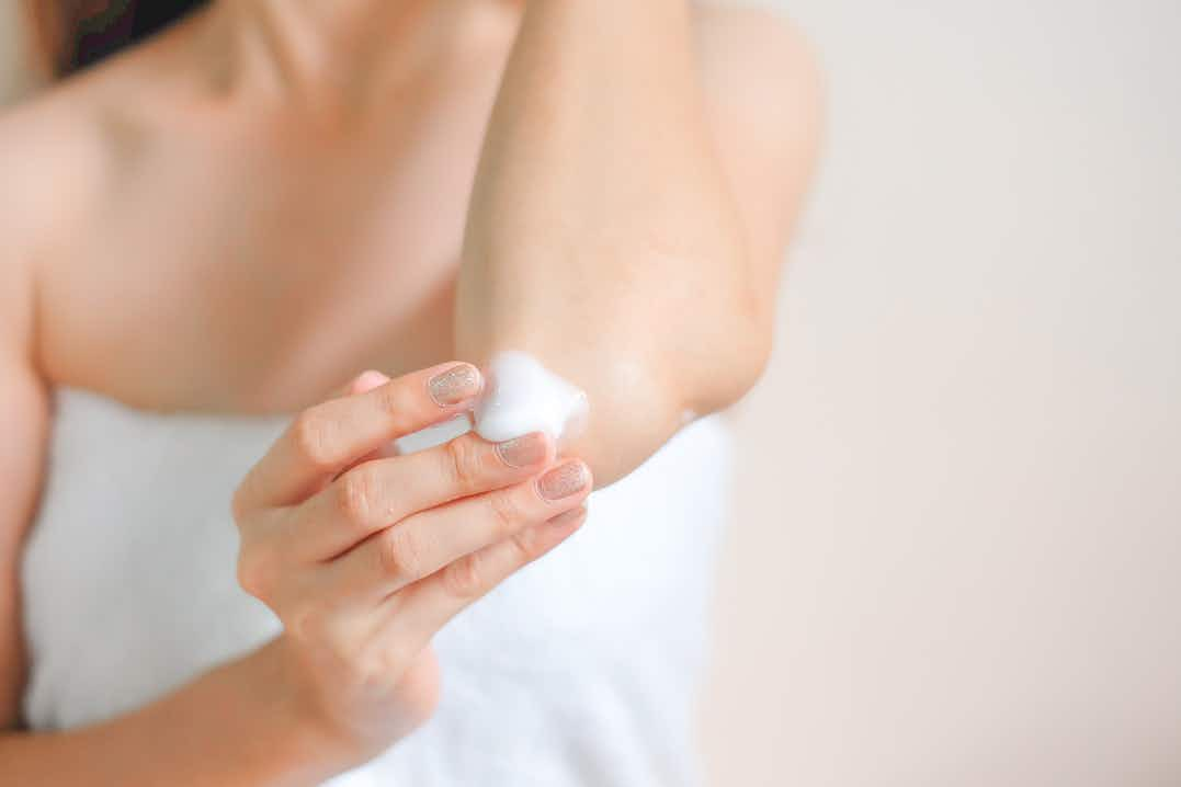 Blurred shoulders and torso of a woman wrapped in white towel, hand massaging white cream into elbow in foreground