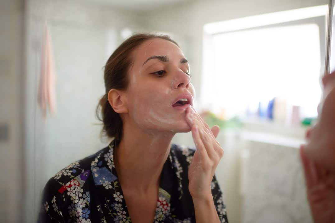 Woman looking in mirror, gently applying cleansing cream to her face, in bathroom wearing floral robe, hair tied back