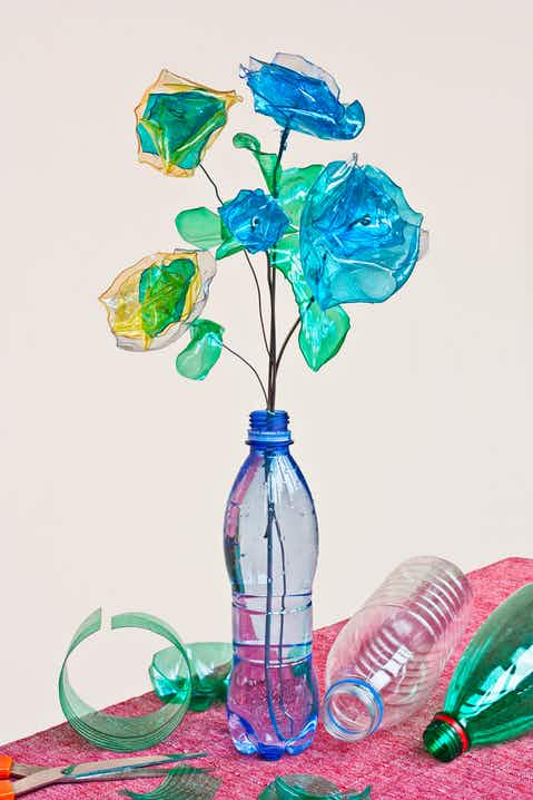 Blue plastic bottle used a vase for blue plastic flowers, surrounded by other plastic bottles on a pink tablecloth