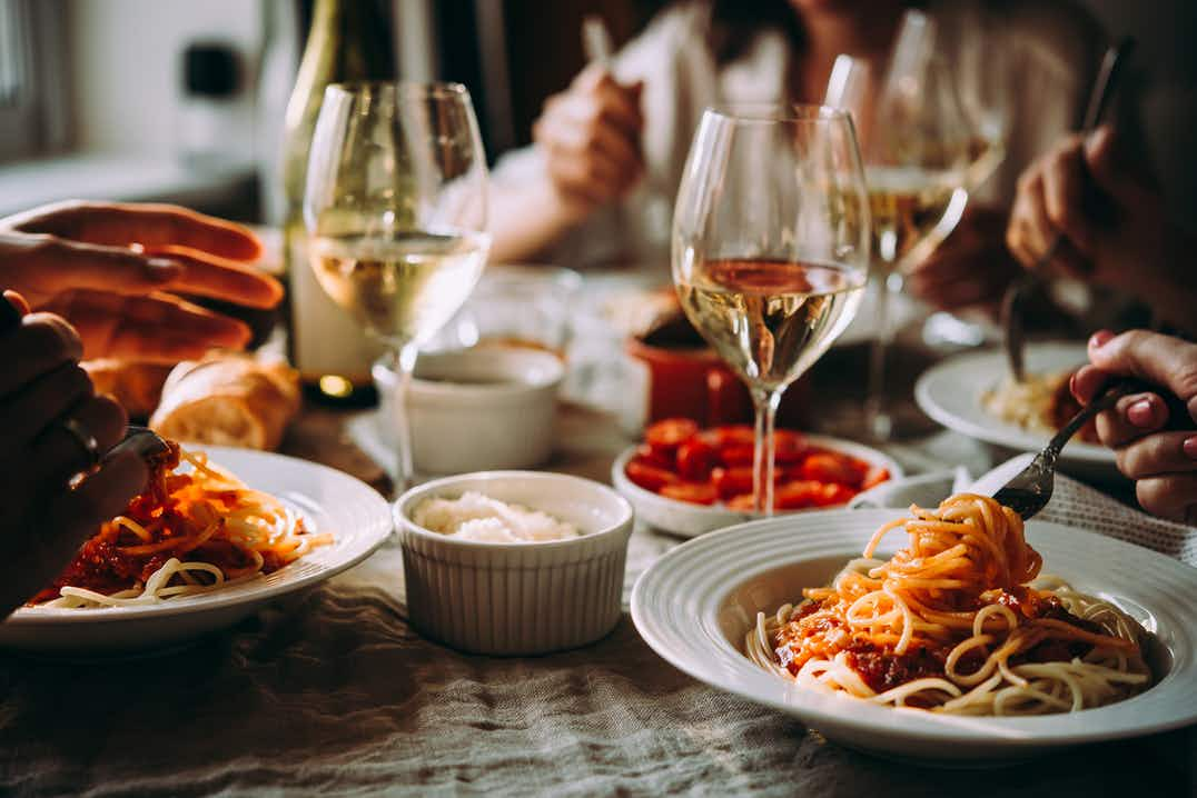 Close-up of dinner table, vegan Bolognese on white plates, white wine in glasses, hands holding cutlery