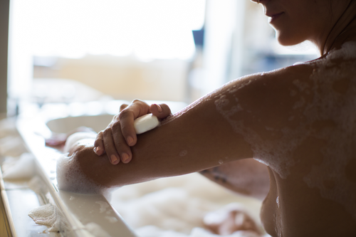 Woman's shoulder and arm in foreground, her right hand smoothing soap bar over her left arm while in a bathtub