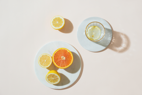 View from above of white plates, one with half orange and two half lemons, one with glass of water with lemon slice