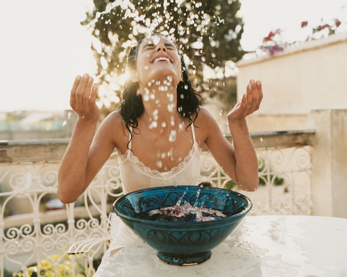 Outdoor terrace, woman sitting at table, splashing water up towards her face from a large teal bowl, blurred background
