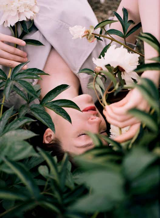 Woman with dark hair lying back against a plant with white flowers, holding flower in hand to smell it