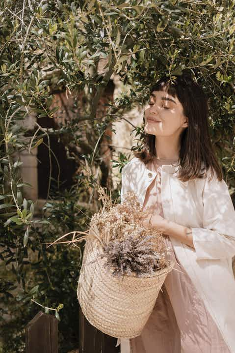 Woman with black hair, eyes closed, wearing white long jacket and holding a basket of dried flowers, next to olive trees
