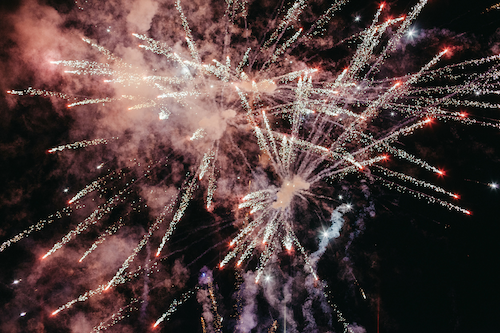 Red and white fireworks going off in different directions with pink smoke against a black sky