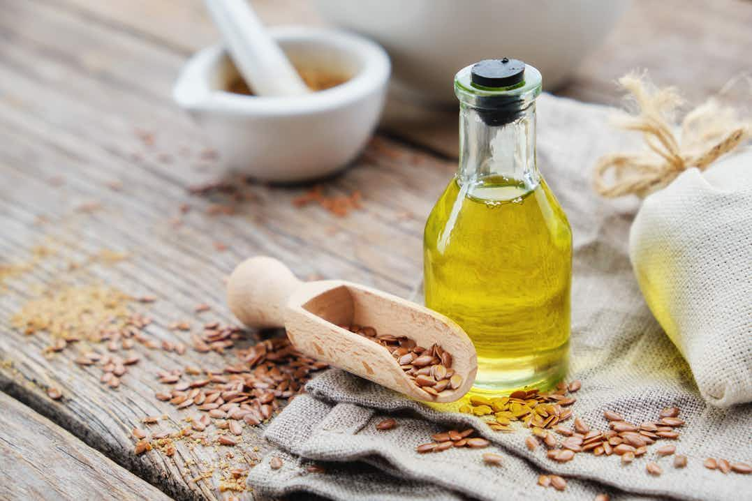 Wooden table with scattered linseeds, small bottle of olive oil, small wooden scoop and pestle and mortar