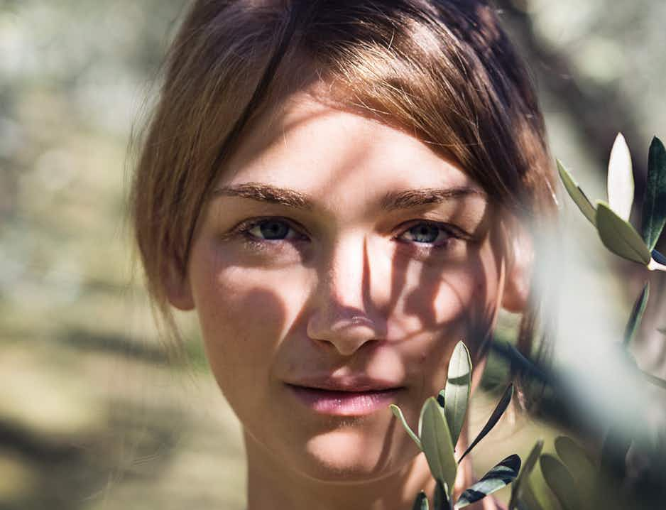 Close-up of woman's face in the sun next to olive branch outdoors, woman looking directly at camera