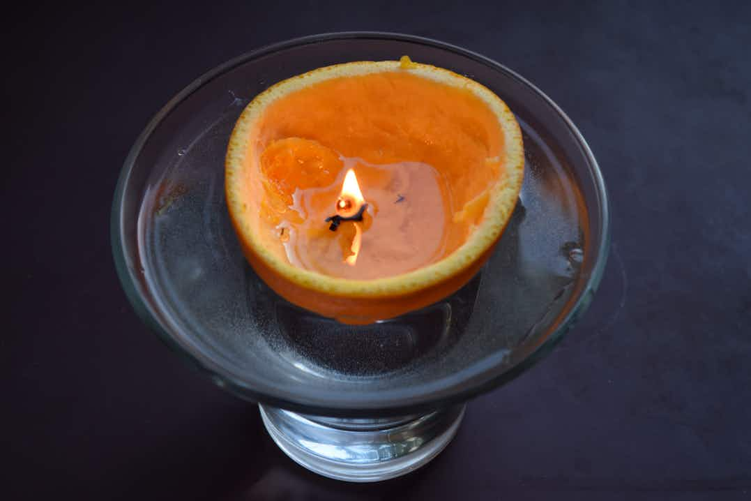 Glass bowl with half an orange peel, filled with olive oil, stalk alight like a candle wick, dark surface background