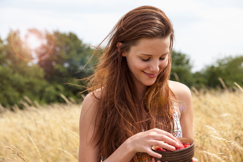 Woman with long dark hair, outdoors in a wheat field selecting a strawberry from a brown bowl, blurred background