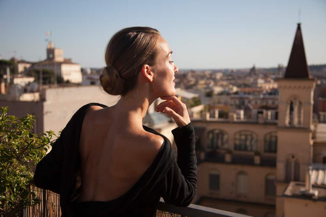 Woman wearing black backless dress, hair in a chignon, overlooking an Italian city panorama in the sun