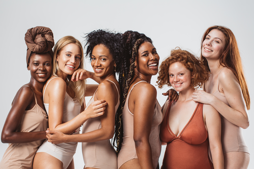 Row of six smiling women with different skin tones and body shapes, all wearing vest tops and pants