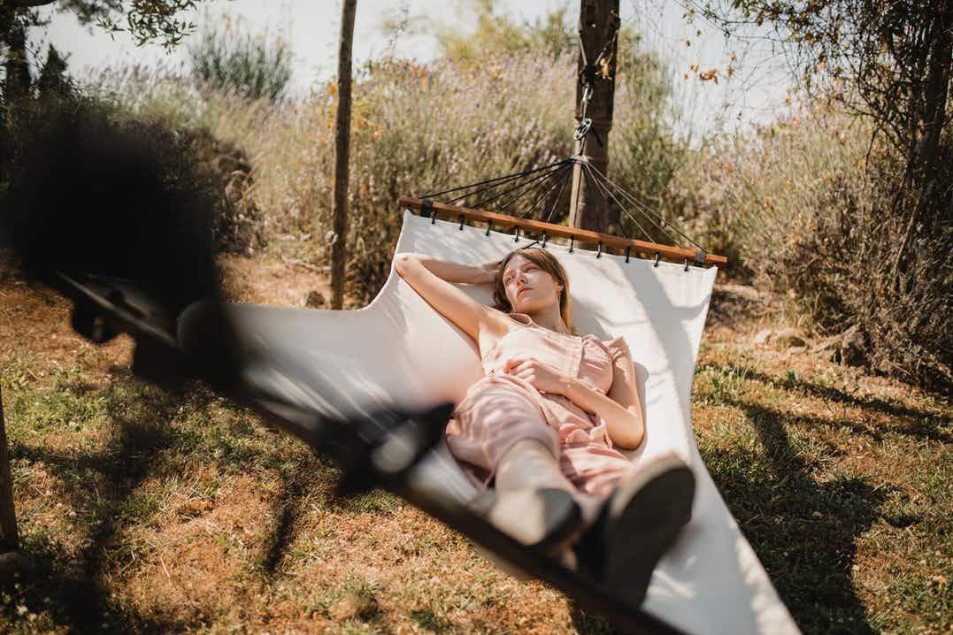 Woman lying back on a white hammock, feet towards camera in garden with dry lawn, trees in background