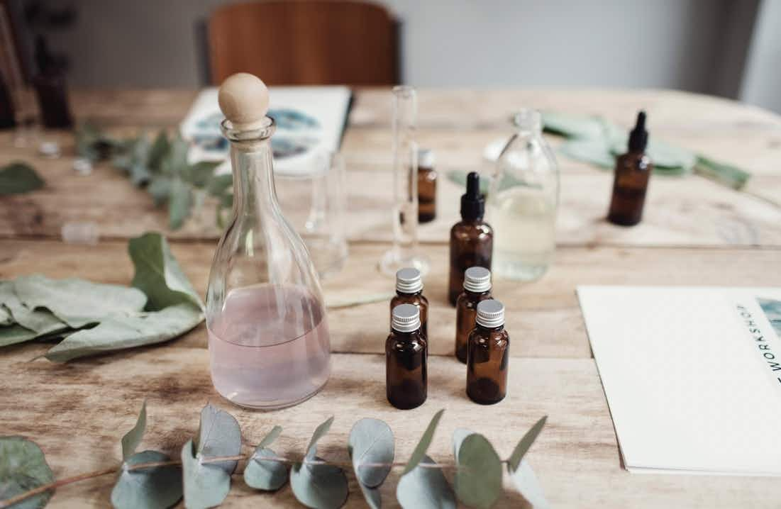Pale wooden table with six small brown glass bottle, one clear tear-shaped bottle with pink liquid inside, various leaves