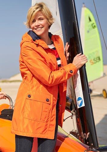 Frau in Orange-farbener Jacke am Strand