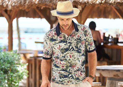 Mann im bunten Polo mit Strohhut_im Hintergrund Strandbar