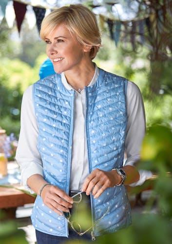 Frau steht im Garten_weiße Bluse, Wetse in hellblau mit weißen Punkten, Blue Jeans