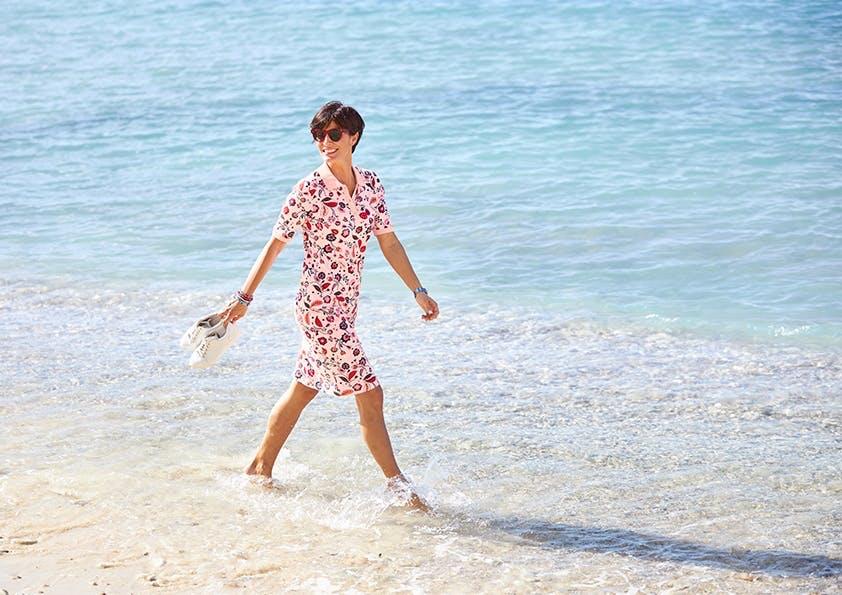 Frau im Polokleid mit Paisley-Muster am Strand.