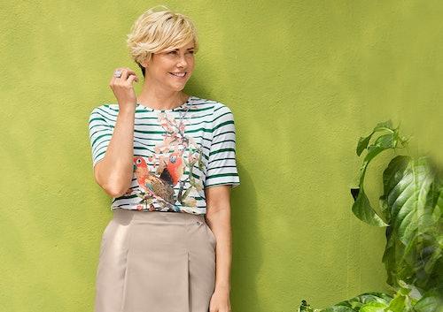 Frau mit geradem, beigem Baumwollrock und grüngestreiftem Shirt mit Papageien.