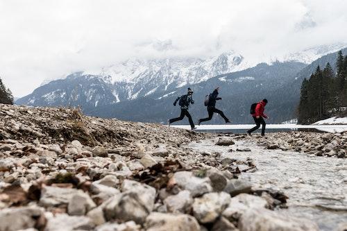 3 Freunde springen über einen Fluss in den Bergen