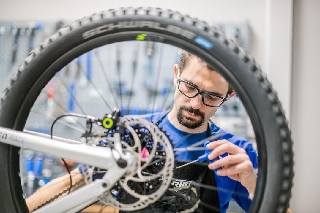 Collaboratore Sportler aggiusta una bicicletta