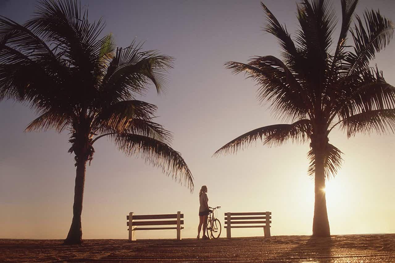 Frau mit Fahrrad am Strand in Florida