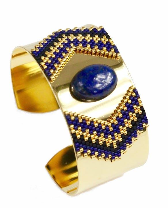 Bracelet manchette en laiton doré à l'Or fin 24 carats orné d'un tissage de perles de verre Miyuki cousues main et d'un cabochon en Lapis Lazuli naturel.Largeur : 30 mmLongueur réglableVertus du Lapis Lazuli: C'est une pierre d'équilibre, d'apaisement, de régulation et de réparation. Symbole de la protection, il aide à traverser les moments et les situations difficiles. C'est une pierre qui apporte sagesse, confiance en soi, intuition et expression créatrice.Matière principale : Or