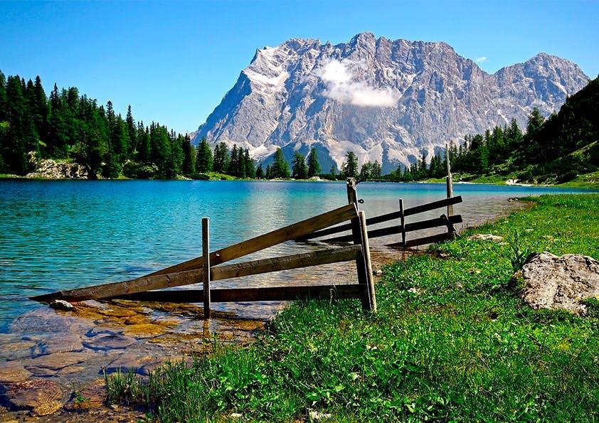 Wiese an einem hellblauen Gewässer mit Zaun. Rundherum Wald und Berge.