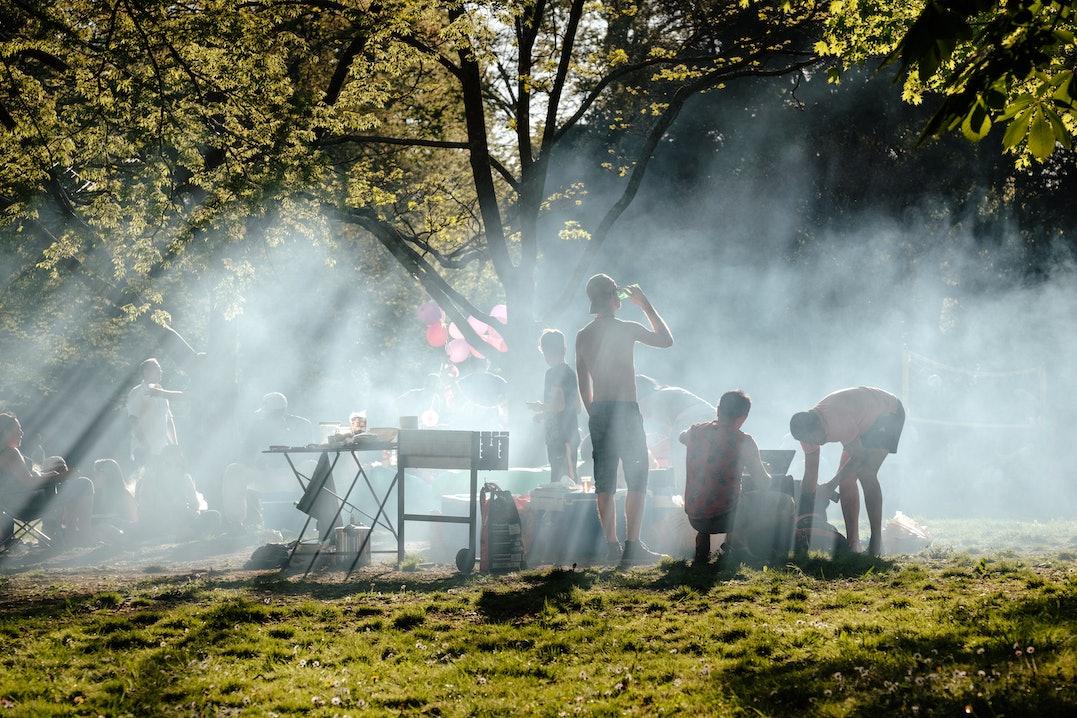 Gruppe von Menschen, die an einem sonnigen Tag in einem Garten grillen
