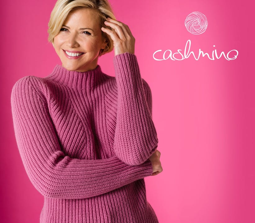 Frau mit blonden kurzen Haaren lächelt und trägt einen pinken Strickpullover.