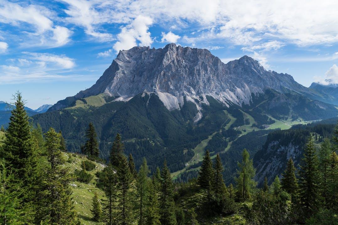 Berg unter einem blauen Himmel mit Wolken. Davor grüne Wiesen und Wald.