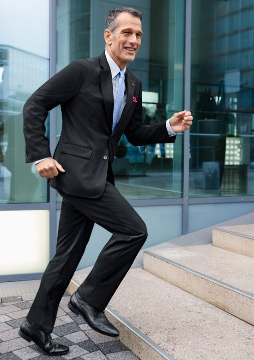 Mann im schwarzen Anzug läuft eine Treppe hoch.