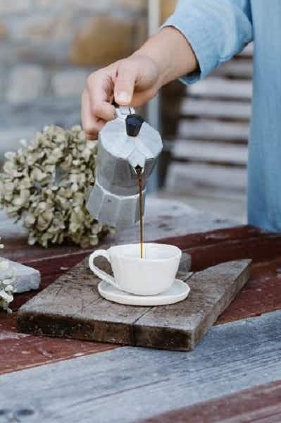 Nainen kaataa vastakeitettyä kahvia perkolaattorista valkoiseen kahvikuppiin. Kuppi on puisella alustalla.
