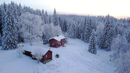 Einsame Hütte in schneebedeckten Wäldern.